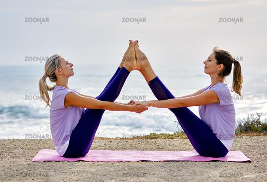 Women doing yoga exercise wide legged boat pose near the sea