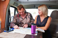 Middle age married couple talking about future travel planning route looking at map sitting inside of recreational vehicle motor home trailer. Active lifestyle