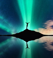Aurora, silhouette of a woman and sky reflection in water