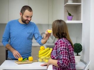 couple cooking food fruit lemon juice at kitchen