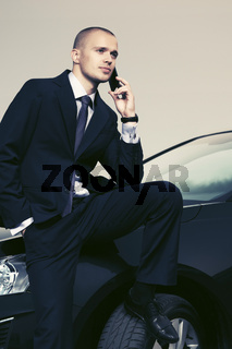 Young businessman calling on cell phone sitting on his car