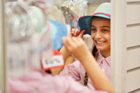 Mädchen beim Hut kaufen in der Anprobe