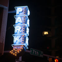 Blue Neon Sign Vertically Stacked Says Park Here