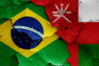 flags of Brazil and Oman painted on cracked wall