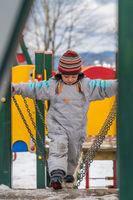 Boy crossing bridge ona playground