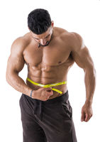 Muscular bodybuilder man measuring belly with tape measure