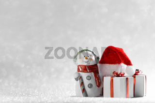 Snowman with christmas gifts and santa hat