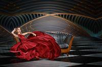 Fashion portrait of beautiful woman in long dress sitting on sofa