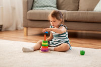 happy baby girl playing with toy blocks at home