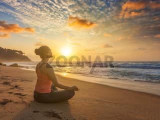 Woman doing yoga oudoors at beach - Padmasana lotus pose