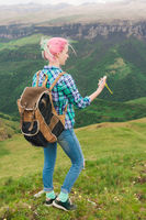 A hipster girl traveled by a blogger in a plaid shirt and with multi-colored hair using a compass standing on a plateau background in the mountains