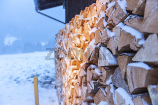 firewood with snow side view by a wooden hut