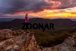 Woman watching storm clouds over Blue Mountains at sunset