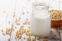 Non-dairy alternative Soy milk or yogurt in mason jar on white wooden table with soybeans in bowl aside