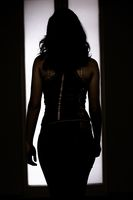 Woman silhouette in front of back-lighted door