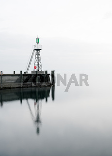 signal light and harbor wall on calm lake waters under an overcast sky negative space abstract