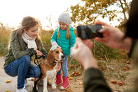 family photographing by smartphone on autumn beach