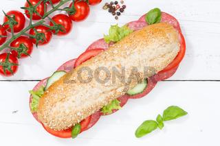 Sandwich Baguette Vollkorn Brötchen belegt mit Salami von oben auf Holzbrett