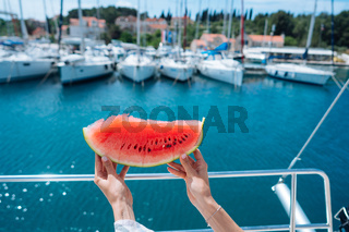 Slice of ripe watermelon in female hands.