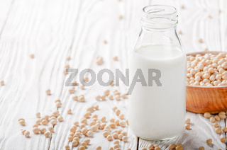 Non-dairy alternative Soy milk or yogurt in glass bottle on white wooden table with soybeans in bowl aside