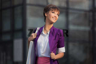 Young fashion business woman in purple blazer with handbag walking at the mall