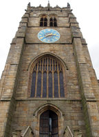 the tower of medieval bradford cathedral in west yorkshire with door and old clock