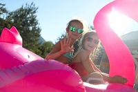 Portrait of two girls wearing sunglasses, happy friends on inflatable flamingo swim float