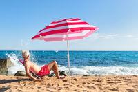 Beach senior man under parasol