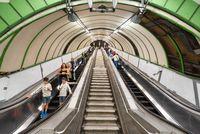 London, United Kingdom - May 12, 2019: View of escalators and travelers inside London Underground.