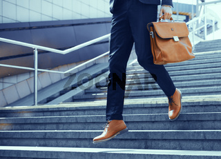 Cropped picture of businessman walking down stairs.