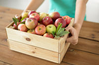 woman with wooden box of ripe apples