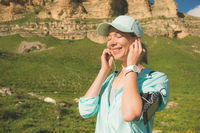 Fitness runner woman closing his eyes listening to music on the nature. Portrait of beautiful girl wearing earphones earbuds and running cap for sun protection