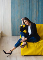 Young woman sitting on yellow sofa