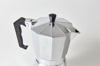 Closeup of metal geyser coffee maker presented on gray background.