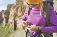 a tourist in sunglasses puts a backpack in the nature on the background of epic rocks preparing for trekking with climbing. The girl hiker fastens the fasteners on the backpack