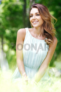 young woman in blue dress sitting on grass young woman in blue dress sitting on grass