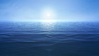 a blue ocean with sun over the horizon