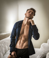 Sexy young man on bed with shirt open chest
