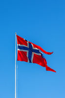 Norwegian flag waving in the wind against a blue sky