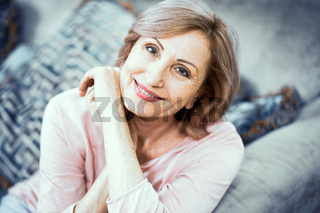 Portrait of a Woman Over 50 Who is Resting at Home in the Living Room.