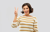 happy smiling woman showing peace or two fingers