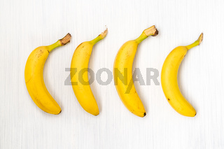 Four fresh bananas on wooden table