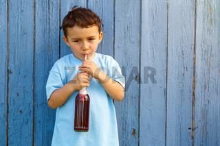 Kind kleiner Junge trinkt Limonade trinken draußen