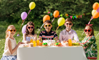 happy kids with cake on birthday party at summer