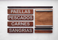 Restaurant menu in spanish on a white wall. Inscriptions of the food and beverage names. Paella, fish, meat and sangria.