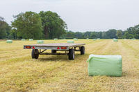 Trailer in grass field with plasticized hay bales