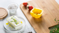 Fresh cheese, peppers and tomatoes on a wooden board on a white kitchen table. Ingredients for salad.