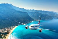 Airplane is flying over amazing mountains with forest and sea