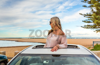 Road trip to beach. Carefree woman in sunroof with views