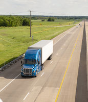 Blue Semi Truck Trailer Rig Hauls Freight on Divided Highway